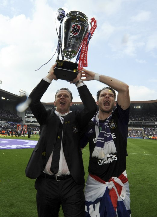 Anderlecht's coach John Van Den Brom and player Bram Nuytinck hold up the trophy after winning the Belgian championship, after drawing Zulte Waregem in Anderlecht
