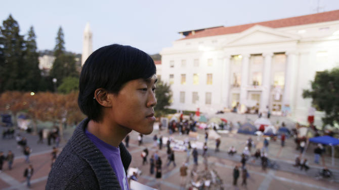 In this photo taken Nov. 16, 2011, Jesse Yeh looks out on the Occupy Cal encampment at Sproul Plaza on the University of California campus in Berkeley, Calif. He  will do just about anything to avoid debt. Yeh uses the university's library instead of buying textbooks. He scrounges for free food and campus events and occasionally skips meals. (AP Photo/Eric Risberg)