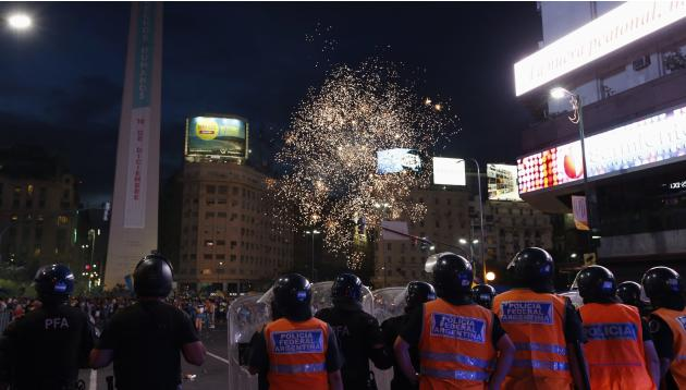 Policemen stand guard as fireworks are set off during celebrations of Argentine soccer team Boca Juniors Fan Day in Buenos Aires