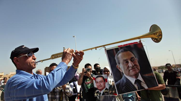 An Egyptian man plays a trumpet as supporters of ousted President Hosni Mubarak, pictured on the trumpet, rally outside a courtroom in Cairo, Egypt, Saturday, May 11, 2013. Egyptian prosecutors say they are presenting new evidence in the retrial of Mubarak. The former president, all in white and wearing sunglasses, attended the hearing in the courtroom defendants' cage alongside his two sons and former interior minister, who was in charge of police at the time. (AP Photo/Khalil Hamra)