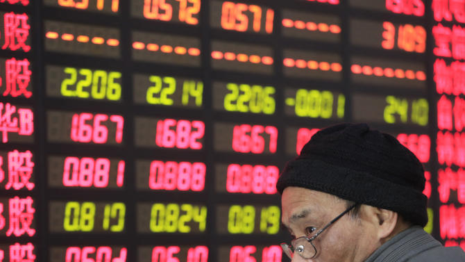 An investor looks at the stock price monitor at a private securities company Thursday Dec. 19, 2013 in Shanghai, China. Asian markets were mixed Thursday after investors took the U.S. Federal Reserve's decision to trim its stimulus as a vote of confidence the American economy is strengthening. China's benchmark Shanghai Composite Index shed 0.1 percent to 2,146.37 after a rise in money market interest rates pushed up the cost of stock trading. (AP Photo)
