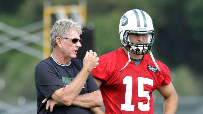 """FILE - In this July 27, 2012, file photo, New York Jets special teams coordinator Mike Westhoff, left, talks with quarterback Tim Tebow on opening day of their NFL football training camp in Cortland, N.Y. Westhoff, the Jets' recently retired special teams coordinator, told a Florida radio station that the way the team handled Tim Tebow was """"an absolute mess."""" (AP Photo/Bill Kostroun, File)"""