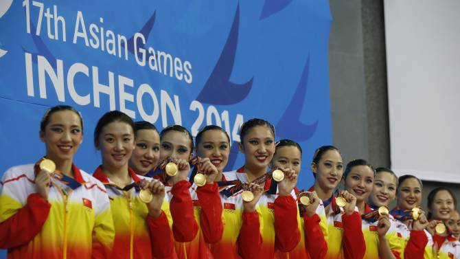 China's team members pose with their gold medals in the Teams Free Combination synchronised swimming final during the 17th Asian Games in Incheon