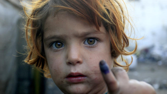 A Pakistani girl shows finger marked after being immunized in Lahore, Pakistan on  Wednesday, Dec. 19, 2012. Gunmen shot dead a woman working on U.N.-backed polio vaccination efforts and her driver in northwestern Pakistan on Wednesday, officials said, raising the number of people killed in the last 48 hours who were part of the immunization drive. (AP Photo/K.M. Chaudary)