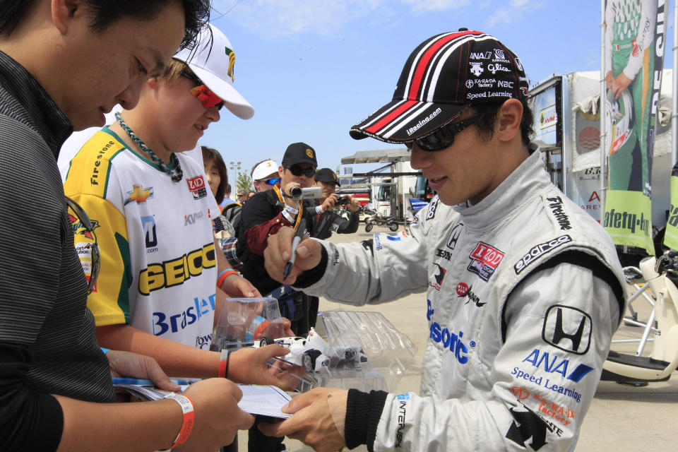 IndyCar driver Takuma Sato, of Japan, signs autographs before the Detroit Grand Prix auto race on Belle Isle in Detroit, Sunday, June 3, 2012. (AP Photo/Carlos Osorio)