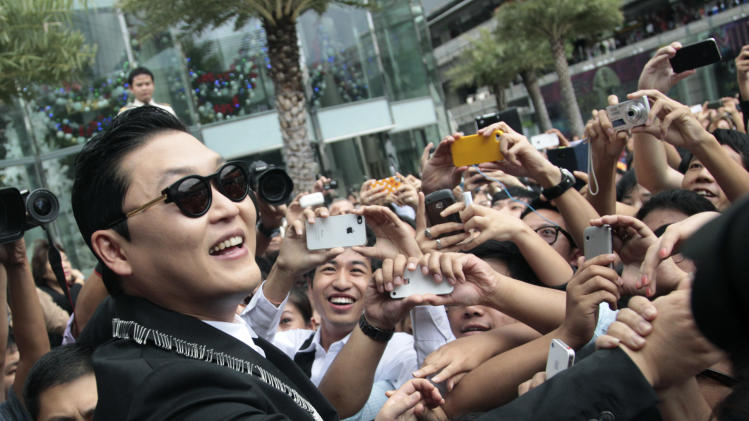 "South Korean rapper PSY, who sings the popular ""Gangnam Style,"" greets Thai fans after a press conference in Bangkok, Thailand, Wednesday, Nov. 28, 2012. PSY will perform in Thailand on Wednesday night -  his first show in Asia outside of South Korea.  (AP Photo/Sakchai Lalit)"