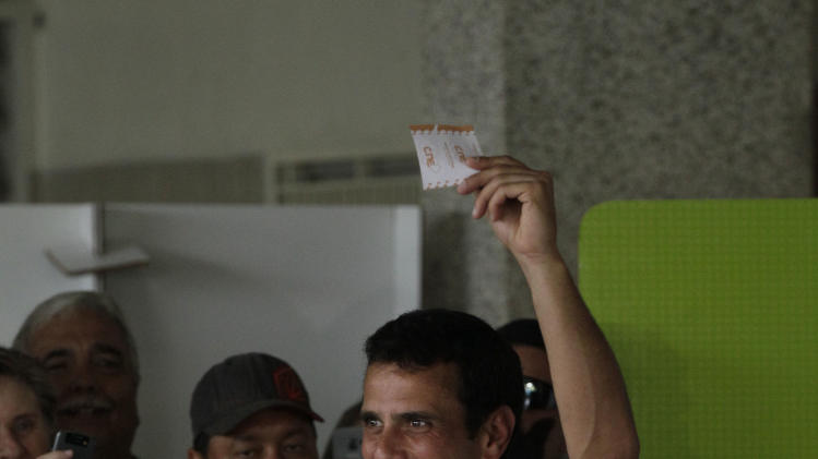 Opposition presidential candidate Henrique Capriles holds up his ballot as he votes in the presidential election in Caracas, Venezuela, Sunday, Oct. 7, 2012. Capriles is running against President Hugo Chavez. (AP Photo/Ariana Cubillos)