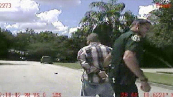 In this still image made from dash-cam video provided by the Lake Mary (Fla.) Police, George Zimmerman is detained by officers on Monday, Sept. 9, 2013. Police in central Florida have been focusing on a broken iPad in their investigation of a domestic dispute between George Zimmerman and his estranged wife Shellie this week. Shellie Zimmerman called 911, saying her estranged husband was in his truck and threatening her and her father with a gun. She also said her husband punched her father in the nose. Hours later, she told police she hadn't seen a gun. (AP Photo/Lake Mary (Fla.) Police)