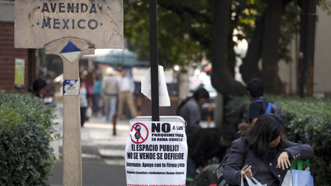 """A woman walks past a sign encouraging a """"no"""" vote in an upcoming referendum regarding the installation of parking meters in the Condesa neighborhood of Mexico City, Friday, Jan. 18, 2013.  Many are vehemently opposed, saying the streets are public and no one should profit from them. But others hope the plan will cut down on cars from elsewhere. On Sunday, Condesa's residents will decide in a referendum whether they want the meters on their streets. (AP Photo/Eduardo Verdugo)"""