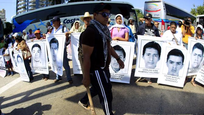 Activists walks past relatives of the 43 missing students from Ayotzinapa Teacher Training College as they block the vehicle of Acapulco's Mayor Luis Walton Aburto during a demonstration in Acapulco, Guerrero