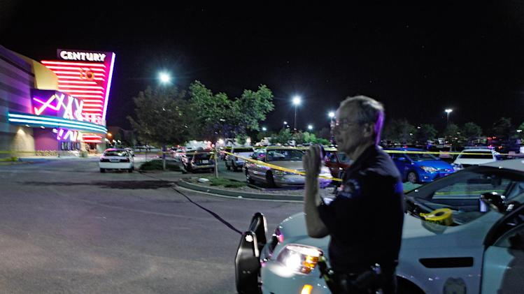 In this July 20, 2012 file photo, an Aurora Police officer talks on his radio outside the Century 16 movie theatre in Aurora, Colo., at the scene of a mass shooting.    It wasn't until more than 20 minutes into the crisis that dispatchers called on the two-person team, but they didn't arrive until more than half an hour after authorities first got word of the shooting. That episode was one of the most glaring examples of ambulance delays that may have cost crucial minutes in the chaotic response to a massacre that ultimately left 12 people dead and dozens wounded.  (AP Photo/Ed Andrieski)