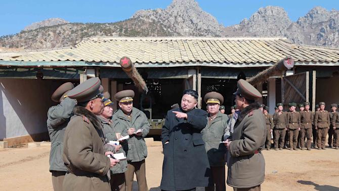"""In this March 11, 2013 photo released by the Korean Central News Agency (KCNA) and distributed March 12, 2013 by the Korea News Service, North Korean leader Kim Jong Un, center, confers with military officers at a long-range artillery sub-unit of KPA Unit 641 during his visit to front-line military units near the western sea border in North Korea near the South's western border island of Baengnyeong. Kim urged front-line troops to be on """"maximum alert"""" for a potential war as a state-run newspaper said Pyongyang had carried out a threat to cancel the 1953 armistice that ended the Korean War.  (AP Photo/KCNA via KNS) JAPAN OUT UNTIL 14 DAYS AFTER THE DAY OF TRANSMISSION"""