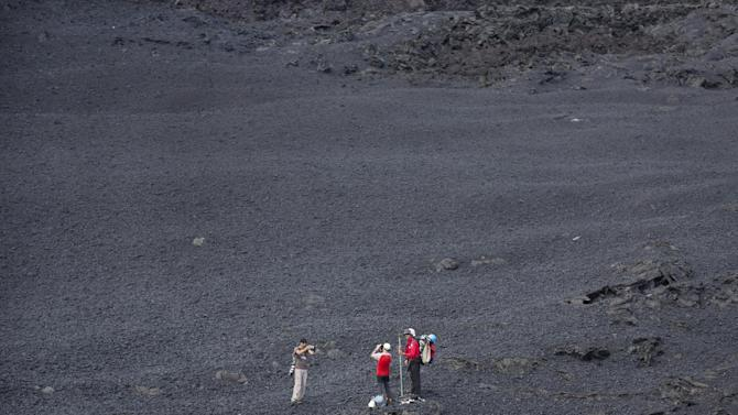 "Volcanologists take photographs of themselves and the volcano as they stand in a field of cooled volcanic rock, as lava erupts nearby from the Piton de la Fournaise ""Peak of the Furnace"" volcano, on the southeastern corner of the Indian Ocean island of Reunion Saturday, Aug. 1, 2015. Spewing red-hot lava, one of the most active volcanoes in the world is currently erupting on this Indian Ocean island, where the world's attention has been focused since a wing fragment believed to be from the missing Malaysian jet was discovered washed up on a beach. (AP Photo/Ben Curtis)"