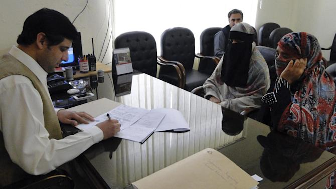 Badam Zari, right, gets her candidacy application for a parliamentary seat checked at the election office in Khar, capital of the  Pakistani tribal area of Bajur on Monday, April 1, 2013. A 40-year-old Pakistani housewife has made history by becoming the first woman to run for parliament from the country's northwest tribal region, a highly conservative area that is a haven for Islamist militants. (AP Photo/Anwarullah Khan)