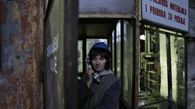 Semsa Hadzo, a Bosnian coal technologist, speaks on the phone while waiting to begin her 8-hour shift at 450 meters underground in the coal mine in Breza, 20 kms north of Sarajevo, Bosnia, on Wednesday, Jan. 16, 2013.  The mine in Breza is the only one in Bosnia where a group of women work deep underground in the coal mines alongside their male colleagues, a legacy of communism, but they're set to retire in three years, marking the end of an era for this community where almost everybody is connected to the coal mine. The shafts and elevators echo with laughter and tales of their grandchildren as women miners work alongside their male counterparts.(AP Photo/Amel Emric)