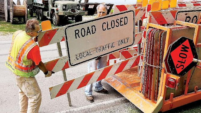 An Illinois Department of Transportation sign crew from Jerseyville, Ill., lays out road closure signs along Route 100 in Grafton, Ill., Tuesday July 8, 2014. Grafton is on the confluence of the Mississippi and Illinois Rivers. The Mississippi River continued its slow rise Tuesday at several Missouri and Illinois towns, but there was reason for optimism after overnight rainfall wasn't as bad as predicted. (AP Photo/The Telegraph, John Badman) BELLEVILLE NEWS-DEMOCRAT OUT; ST. LOUIS POST-DISPATCH OUT