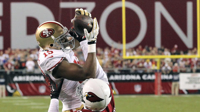 San Francisco 49ers wide receiver Michael Crabtree (15) pulls in a touchdown pass as Arizona Cardinals cornerback Patrick Peterson (21) defends during the first half of an NFL football game, Monday, Oct. 29, 2012, in Glendale, Ariz.  (AP Photo/Ross D. Franklin)