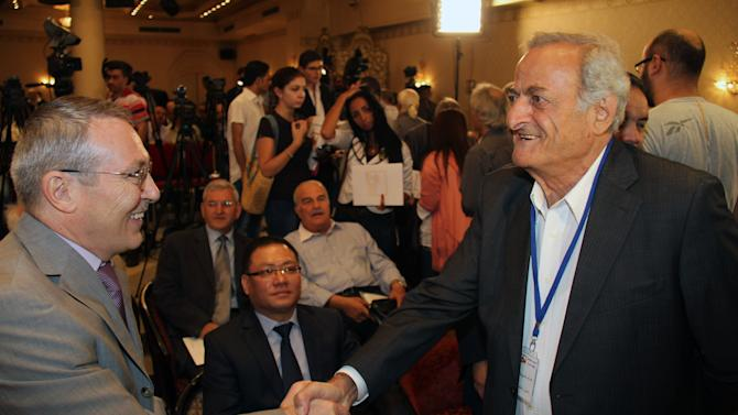 The Russian Ambassador in Damascus, Azmat Allah Kolmahmedov, left, greets Aref Dalila, a Syrian opposition figure at the opening session of a conference of some 16 opposition parties headed by the National Coordination Body for Democratic Change in Syria, an opposition group made up mostly of Syria-based opposition personalities, in Damascus, Syria, September 23, 2012. The rare opposition gathering in a regime-held city, which called for the overthrow of the Syrian regime, was attended by the Ambassadors from China and Russia, both countries that support Assad, suggesting the regime authorized the conference to bolster its own rhetoric that there should be a peaceful settlement to the Syrian crisis through dialog. (AP Photo/Bassem Tellawi)