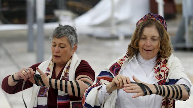 """Members of the activist group, """"Women of the Wall"""", wear Jewish prayer shawls and tefillin during an event teaching people how to put on the tefillin, near the Western Wall in Jerusalem's Old City"""