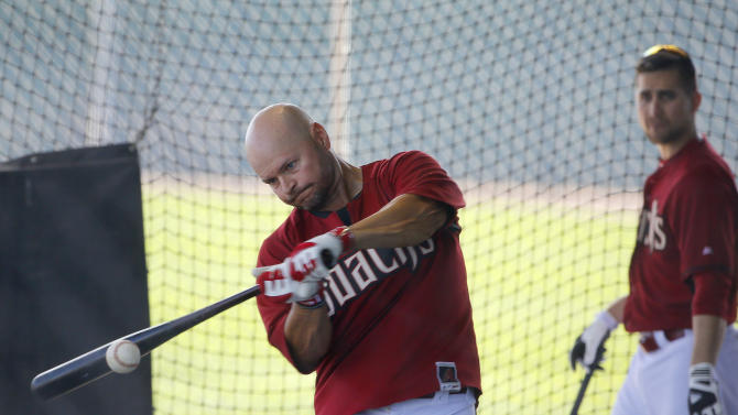 Arizona Diamondbacks' Cody Ross, left, connects on a baseball as teammate Ender Inciarte watches as they hit from the batting cages during baseball spring training Thursday, Feb. 26, 2015, in Scottsdale, Ariz. (AP Photo/Ross D. Franklin)