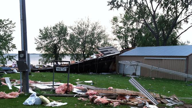 Siding and fiberglass insulation from a cabin on Lake Poinsett lie on the ground after a fast-moving line of strong storms barreled across northeast South Dakota and spawned several tornadoes, Friday, June 21, 2013, at Lake Poinsett, S.D. One woman was killed when her trailer was tossed in the air from the storms. (AP Photo/Tena Haraldson)