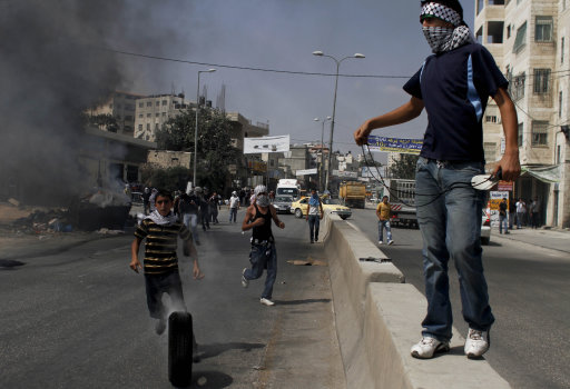 A Palestinian demonstrator holds a slingshot as others roll tires to burn during clashes with Israeli soldiers, not seen, during a protest at the Qalandia checkpoint between the West Bank city of Ramallah and Jerusalem, Wednesday, Sept. 21, 2011. Palestinians clashed with Israeli security forces in Qalandia Wednesday, as thousands of flag-waving Palestinians rallied in towns across the West Bank to show support for their president's bid to win U.N. recognition of a Palestinian state. (AP Photo/Tara Todras-Whitehill)