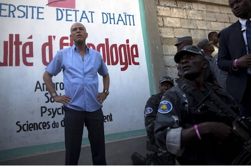 Haiti's President Michel Martelly stands at an entrance to the University of Haiti in Port-au-Prince, Haiti, Friday, Feb. 17, 2012. Martelly's office said him and his accompanying motorcade were attacked while he strolled through the capital's downtown area in a Carnival procession. Witnesses say rocks were thrown at him from behind the university building. Martelly was taken without injury to the nearby National Palace, but left it about an hour later and proceeded around the campus. (AP Photo/Ramon Espinosa)