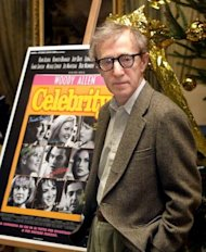 "US director Woody Allen poses for photographers next to his film poster for ""Celebrity"" prior a to press conference for its promotion in 1998. Woody Allen says he can't stand watching any of his own films -- but the 76-year-old US filmmaker insists he has no plans to retire"