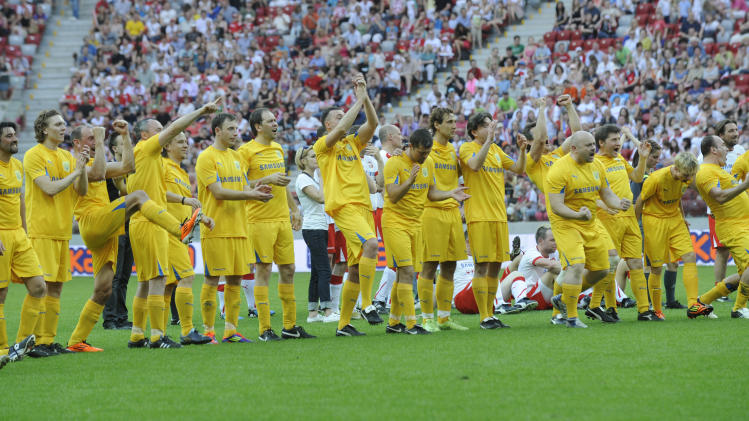 Members of the Ukrainian team react after Polish and Ukrainian celebrities played a friendly soccer match at the National Stadium in Warsaw, Poland, Sunday, April 29, 2012. The game was the last event at the site before the opening of the Euro 2012 soccer championships, which will open in this stadium. (AP Photo/Alik Keplicz)