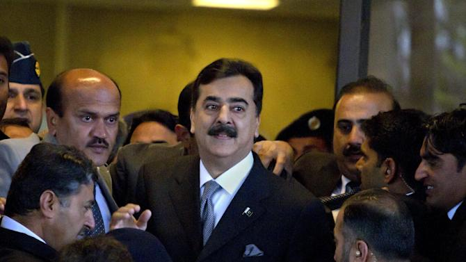 FILE - In this Feb. 13, 2012 file photo, Pakistani Prime Minister Yousuf Raza Gilani, center, is surrounded by security personnel as he arrives at Supreme Court for a hearing in Islamabad, Pakistan. The lawyer for Pakistan's prime minister says on Tuesday, April 24, 2012 the Supreme Court is expected to deliver its verdict Thursday in a contempt case against his client. Gilani was charged after he refused to reopen an old corruption case against the president. (AP Photo/Anjum Naveed, File)
