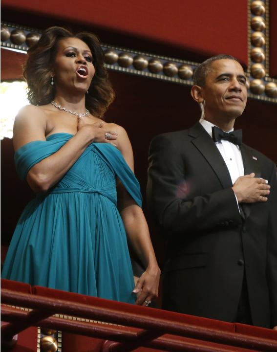 U.S. first lady Michelle Obama and President Barack Obama listen to the national anthem at the start of the Kennedy Center Honors at the Kennedy Center in Washington