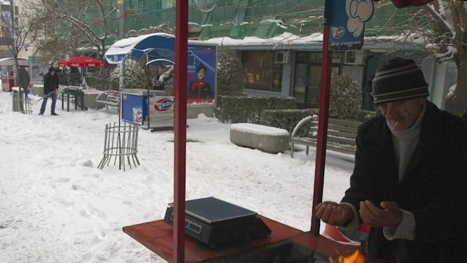 A street vendor warms his hands over a coal fire in Pristina, Kosovo Tuesday, Dec. 11, 2012. Weather forecasts predict cold temperatures and snow for Eastern Europe during the upcoming days. (AP Photo/Visar Kryeziu )