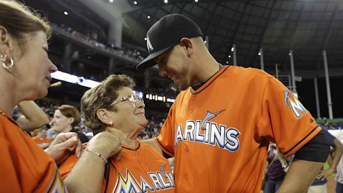 Miami Marlins starting pitcher Jose Fernandez, right, talks with his grandmother Olga Fernandez, of Cuba, center, and mother Maritza Fernandez, left, of Miami, following the Marlins' 10-1 victory over the Colorado Rockies in an opening day baseball game, Monday, March 31, 2014, in Miami