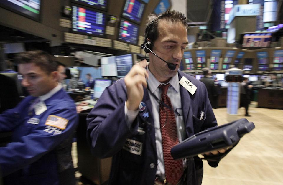 Trader Gregory Rowe, right, works on the floor of the New York Stock Exchange Monday, Aug. 22, 2011. (AP Photo/Richard Drew)