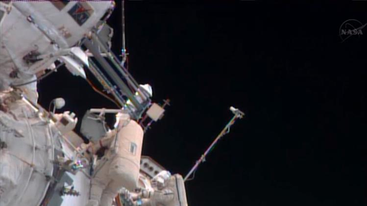 In this image made from video provided by NASA, Russian cosmonauts Pavel Vinogradov, left, and Roman Romanenko perform a spacewalk outside the International Space Station to gather old science experiments and install new ones, and replace a navigation device. (AP Photo/NASA)
