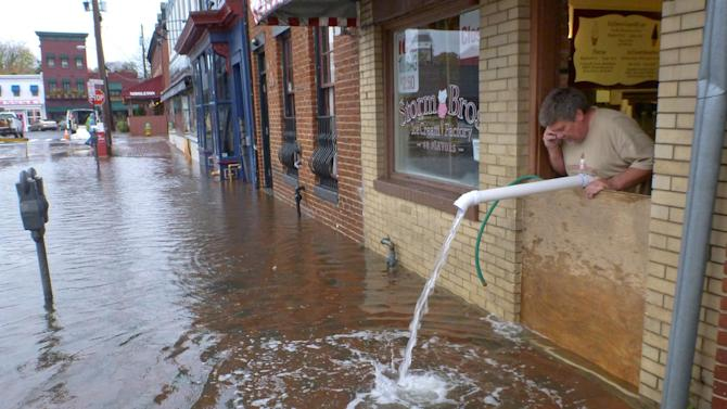 Sveinn Storm pumps water out of his flooded Storm Bros. Ice Cream Factory store  in downtown Annapolis, Md. on Tuesday, Oct. 30, 2012, in the aftermath of Hurricane Sandy. High tide swept over the banks of the city dock, flooding lower Annapolis stores. (AP Photo/Blake Sell)