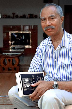 """FILE - This July 4, 2000 file photo shows Hans Massaquoi holding his recently published book """"Destined to Witness: Growing up Black in Nazi Germany,"""" at his home in New Orleans, La. Massaquoi, the former managing editor of Ebony magazine, has died, Saturday, Jan. 19, 2013 on his 87th birthday, in Jacksonville, Fla. (AP Photo/Matthew P. D'Agostino, file)"""