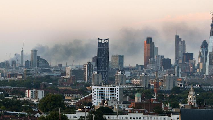 A general view of the London skyline Tuesday evening, Aug. 9 2011,  with smoke still seen from the Sony DADC warehouse in Enfield, north London, after rioting in the area last night.   Britain began flooding London's streets with 16,000 police officers Tuesday, nearly tripling their presence as the nation feared its worst rioting in a generation would stretch into a fourth night. The violence has turned buildings into burnt out carcasses, triggered massive looting and spread to other U.K. cities.   (AP Photo / Lewis Whyld/PA )  UNITED KINGDOM OUT