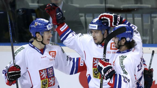 Czech Republic's Kovar celebrates with team mates Radil and Zatovic after scoring against Sweden during their Euro Hockey Tour ice hockey match in Prague