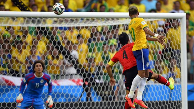 Brazil's forward Neymar (R) and Mexico's defender Rafael Marquez (C) jump for the ball in front of Mexico's goalkeeper Guillermo Ochoa during a World Cup match in Fortaleza on June 17, 2014