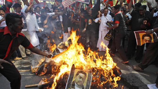 Indian Tamil activists of the Marumalarchi Dravida Munnetra Kazhagam (MDMK) party burn an effigy and portraits of Sri Lankan President Mahinda Rajapaksa during a protest in New Delhi, India, Friday, Feb. 8, 2013. Various pro-Tamil groups and leaders are protesting Rajapaksa's visit holding him responsible for the killing of innocent Tamils during the civil war in Sri Lanka. Rajapaksa is on a personal visit to the country. (AP Photo/Tsering Topgyal)