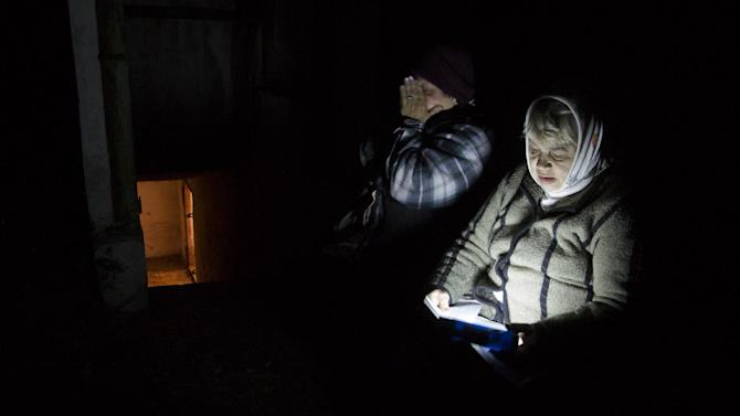 Local resident Galina Dudkina, right, reads poems near an entrance to a bomb shelter, as she and her neighbour go out for fresh air, during a short cease fire, in the Petrovsky of Donetsk, eastern Ukraine Tuesday, Aug. 5, 2014. (AP Photo/Dmitry Lovetsky)
