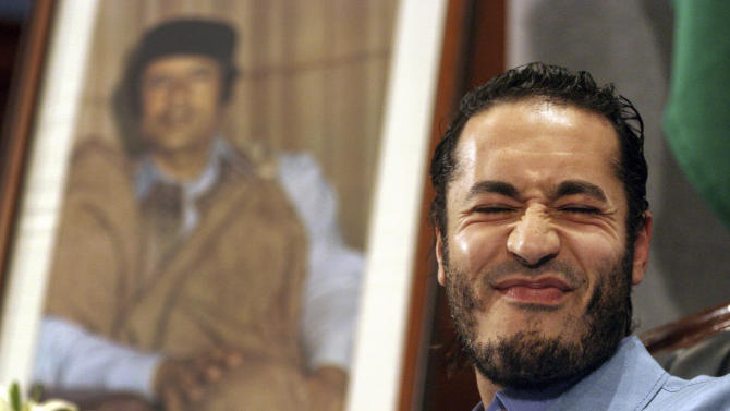 "FILE -- In this file photo of  Monday, Feb. 7, 2005 Al-Saadi Gadhafi, the son of Libyan leader Moammar Gadhafi, reacts in front of the leader's portrait during a press conference in Sydney, Australia. The spokesman for Niger's government announced Sunday Sept, 11, 2011 that Libyan leader Moammar Gadhafi's son Al-Saadi has entered the country via the northern desert separating the landlocked African nation from Libya.  Amadou Morou, who is also the minister of justice, told reporters at a news conference Sunday: ""I wish to announce to you that one of Gadhafi's sons _ Al-Saadi Gadhafi _ was intercepted in the north of Niger.""(AP Photo/Dan Peled, file)"