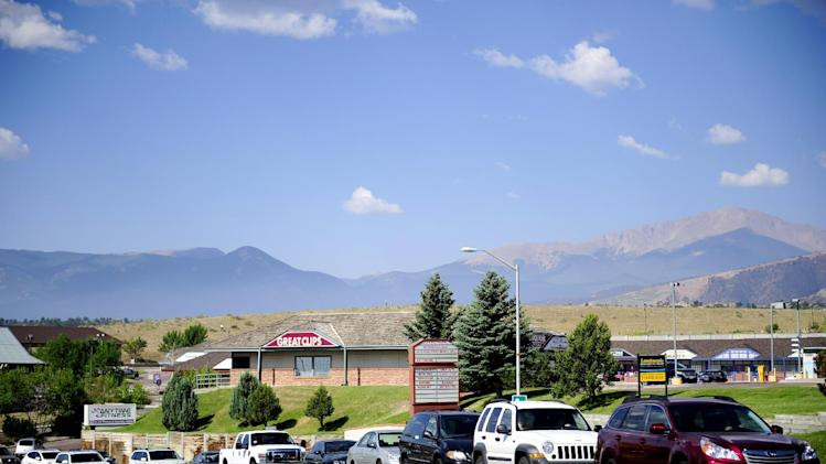 Cars wait in a traffic line on Vindicator Drive to check in at Eagleview Middle School in order to view their homes Sunday, July 1, 2012, in Colorado Springs, Colo. Even people who know their homes are still standing have some anxiety over temporary visits being allowed today to wildfire-devastated neighborhoods around Colorado Springs. About 10,000 people are still out of their homes, having been among 30,000 who initially fled the most destructive fire in Colorado's history.(AP Photo/The Colorado Springs Gazette, Susannah Kay)