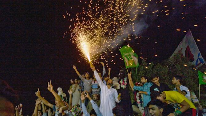 A supporter of Pakistan Muslim League-N party releases fireworks to celebrate their party victory in the parliamentary election outside the party's headquarters in Lahore, Pakistan, Sunday, May 12, 2013. Former Pakistani Prime Minister Nawaz Sharif looked set Sunday to return to power for a third term, with an overwhelming election tally that just weeks ago seemed out of reach for a man who had been ousted by a coup and was exiled abroad before clawing his way back as an opposition leader. (AP Photo/Anjum Naveed)