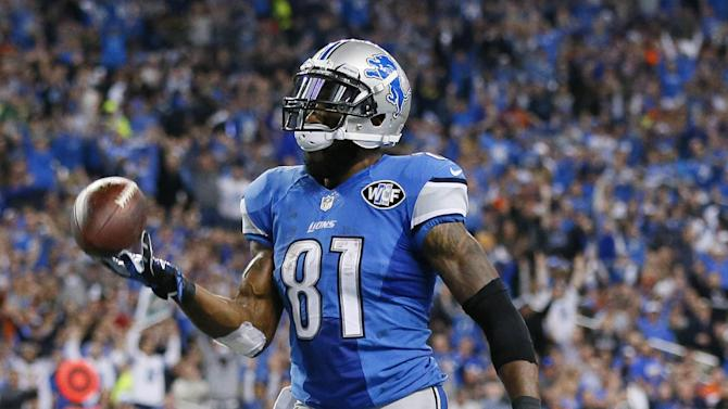 Detroit Lions wide receiver Calvin Johnson tosses the ball after his 25-yard reception for a touchdown during the first half of an NFL football game against the Chicago Bears in Detroit, Thursday, Nov. 27, 2014