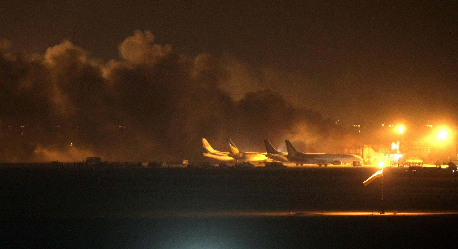 Fire illuminates the sky above Karachi airport terminal where security forces are fighting with attackers Sunday night, June 8, 2014, in Pakistan. Gunmen disguised as police guards attacked the terminal with machine guns and a rocket launcher during a five-hour siege that killed 13 people as explosions echoed into the night, while security forces retaliated and killed all the attackers, officials said Monday. (AP Photo/Fareed Khan)