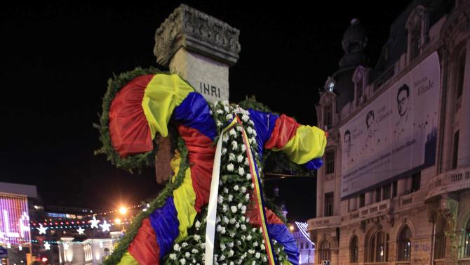 A man arranges wreaths around a cross during the 25th anniversary of the country's 1989 revolution in central Bucharest