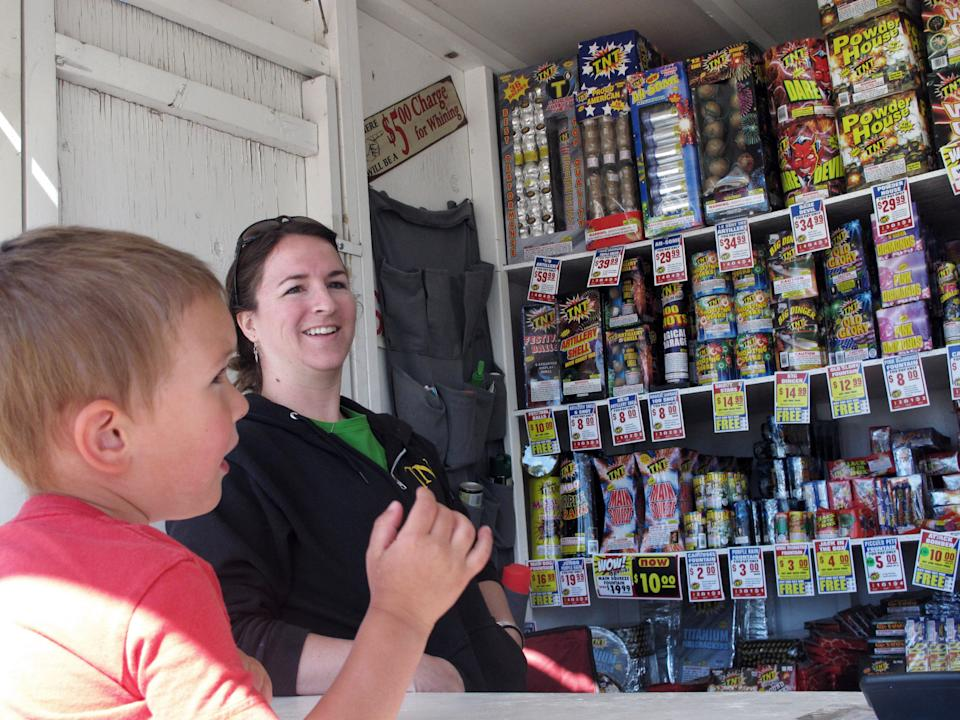 In this Thursday, June 28, 2012 photo, Clinton Kendall, 3, looks at fireworks for sale while the stand's owner, Anna Richards, looks on in Helena, Mont. Montana officials have urged people not to shoot fireworks while extreme wildfire conditions exist. (AP Photo/Matt Volz)