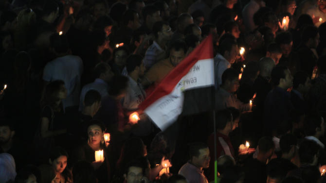 Egyptians light candles at Talat Harb square in downtown Cairo, Egypt, Thursday, Oct. 13, 2011, to mourn more than two dozen people who were killed when Christians, angered by a recent church attack, clashed Sunday night with Muslims and security forces outside the state television building in central Cairo. Egyptian flag is at center. (AP Photo/Amr Nabil)